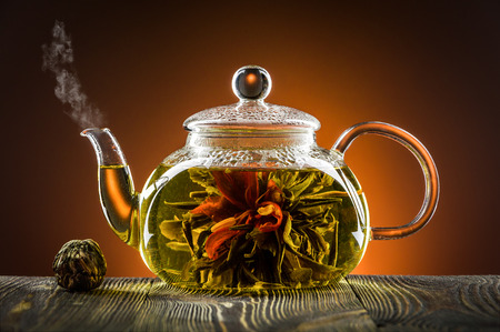 Glass teapot with blooming tea flower on wooden table photo