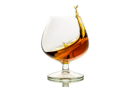 The glass with splashes brandy isolated