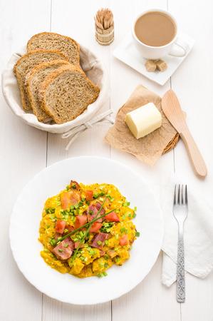 scrambled eggs: Huevos revueltos y tocino en la mesa blanca