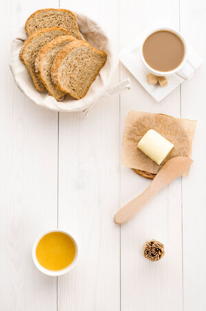 Breakfast including  bread, honey, butter and coffee photo