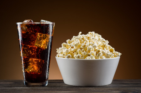 coke: Popcorn and coke on the table