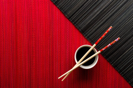 Chopsticks and bowl with soy sauce on bamboo mat photo