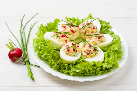 Stuffed eggs on lettuce with chives garnish