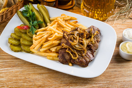 Roast beef, french fries and jug of beer on the rural table photo
