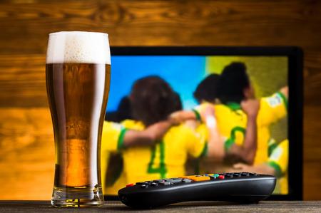 ビールとテレビのリモコン、バック グラウンドでサッカーの試合のガラス 写真素材