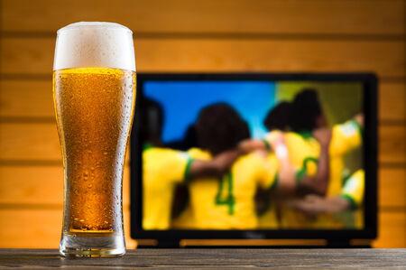 Een glas koud bier op tafel, voetbalwedstrijd in de achtergrond Stockfoto