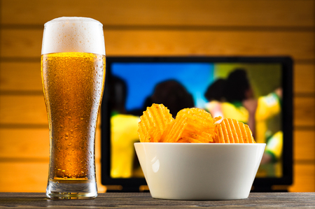 un bottled: Glass of cold beer and chips, football match in background