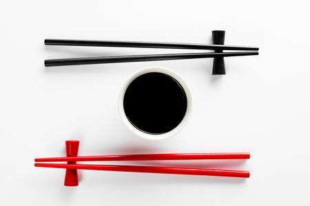 Eetstokjes en kom met sojasaus op witte achtergrond Stockfoto