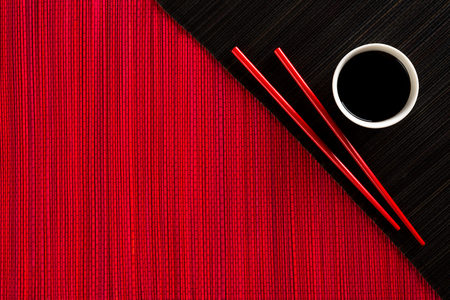 japanese cuisine: Chopsticks and bowl with soy sauce on bamboo mat