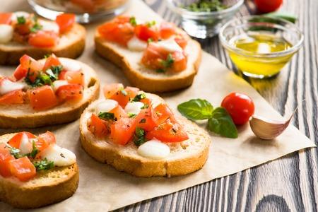 Bruschetta mit gebratenen Tomaten, Mozzarella-Käse, Knoblauch und Basilikum Standard-Bild - 33233360
