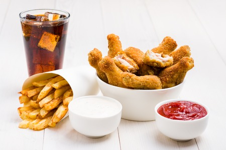 Chicken wings, french fries, coke and sauces on the table 免版税图像