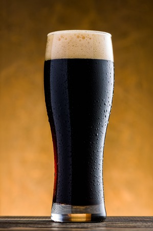 dark beer: Glass of cold dark beer on wooden table Stock Photo