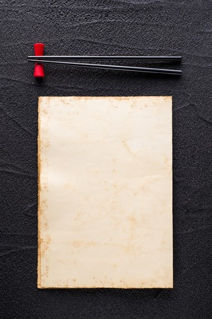 Chopsticks and restaurant menu concept on black rock