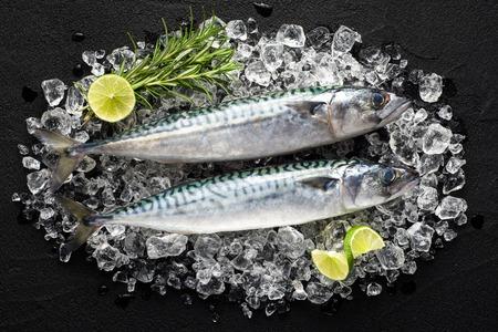 新鮮な魚を氷の黒の石のテーブルの上に表示します。