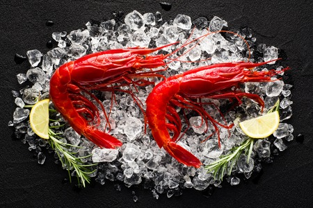 Fresh big red shrimp on ice on a black stone table top view Stok Fotoğraf