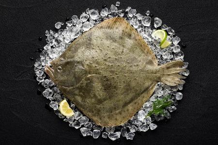 Verse tarbot vissen op ijs op een zwarte stenen tafel bovenaanzicht