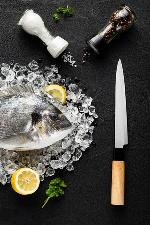 Fresh dorado fish on ice on a black stone table top view Stock Photo