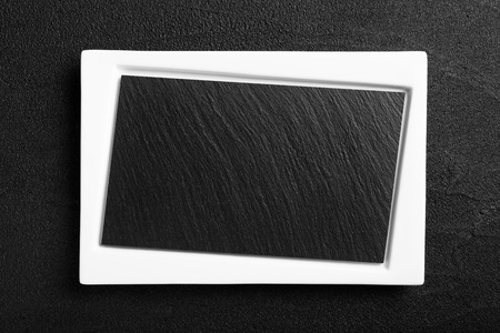 Empty white plate with black stone surface photo