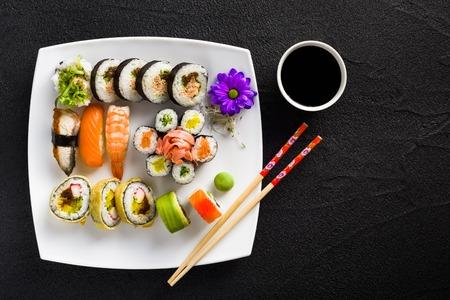 comida japonesa: Sushi en el plato blanco sobre una mesa de piedra negro