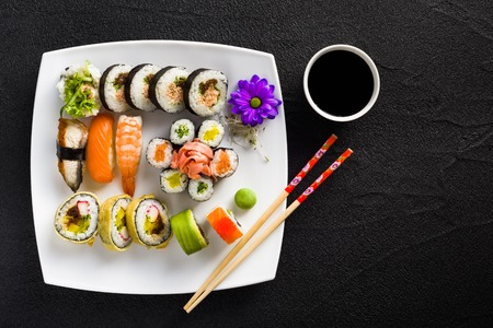 Sushi on white plate on a black stone table