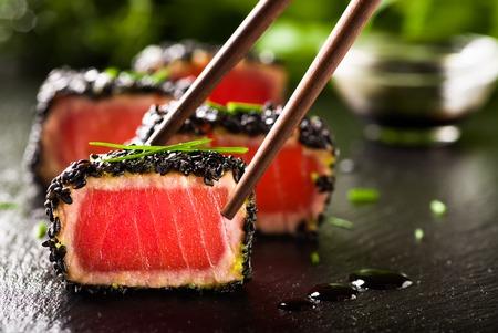 Gebakken tonijnsteak in zwarte sesam met eetstokjes Stockfoto