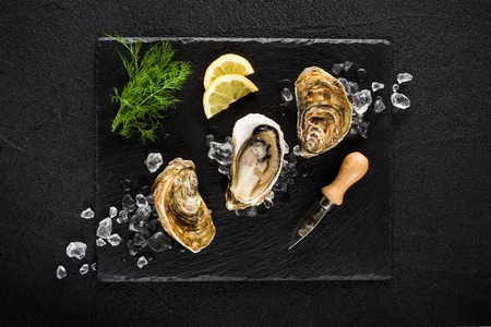 aphrodisiac: Fresh oysters on a black stone plate top view