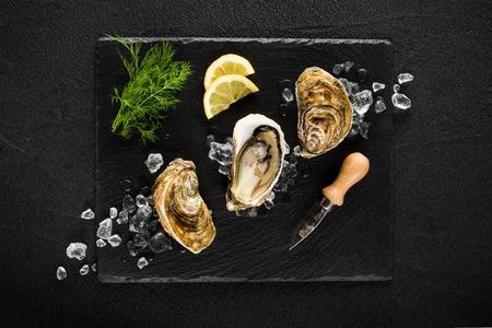 Verse oesters op een zwarte stenen plaat bovenaanzicht Stockfoto