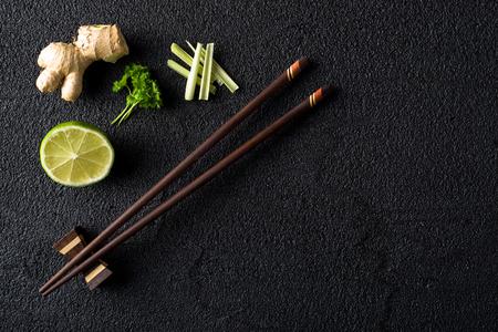 Eetstokjes en voedselingrediënten op zwarte stenen tafel bovenaanzicht Stockfoto