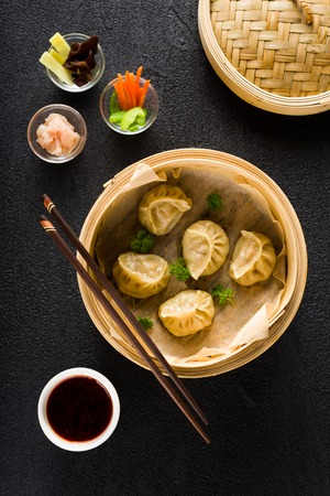 street food: Dim sum dumplings in steamer and ingredients top view