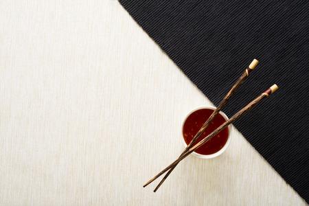 Eetstokjes en kom met saus op tafel mat bovenaanzicht