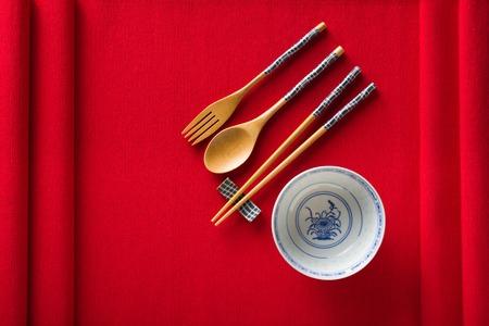 Chinese kom, vork, lepel en eetstokjes op rode mat bovenaanzicht