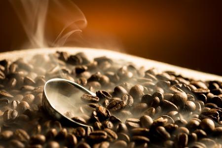 Roosteren koffiebonen met rook op donkere achtergrond