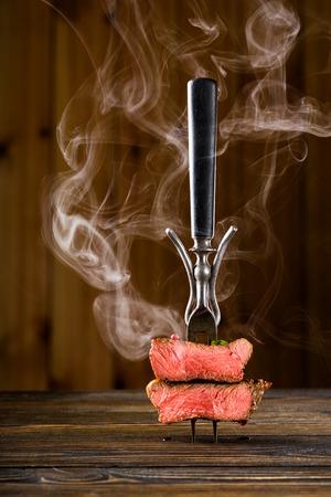 나무 테이블에 포크에 얇게 썬 쇠고기 스테이크