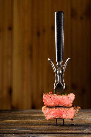 Sliced beef steak on a fork on the wooden table Banco de Imagens