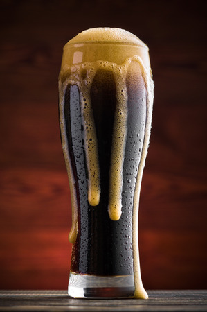 Glass of cold dark beer on wooden table Zdjęcie Seryjne
