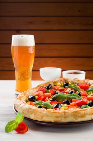 ピザと木製のテーブルの上のビールのグラス 写真素材
