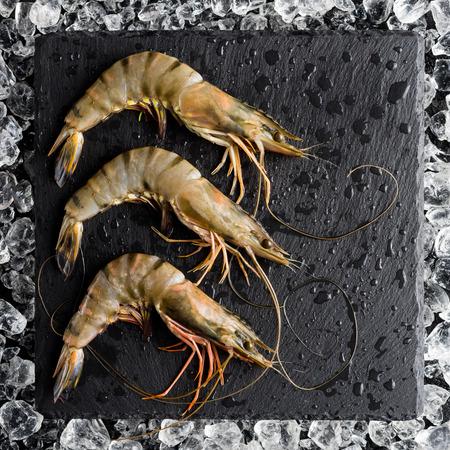 tiger shrimp: Fresh tiger shrimp on ice on a black stone table top view Stock Photo