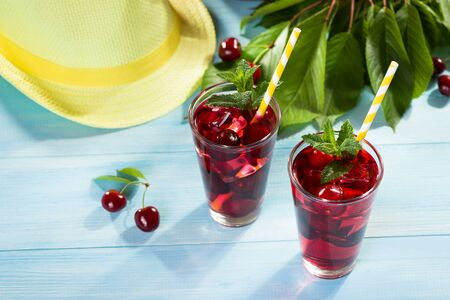 cherry: Glass of cherry juice on blue wooden table