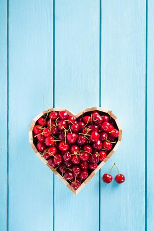 corazones azules: Cerezas en un cuadro de corazón en azul Vista madera mesa