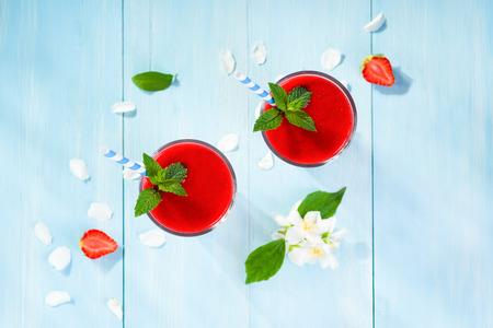 erdbeer smoothie: Erdbeer-Smoothie und Bl�tenbl�tter auf blauem Hintergrund Ansicht von oben Lizenzfreie Bilder