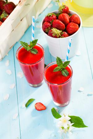 erdbeer smoothie: Erdbeer-Smoothie und Bl�tenbl�tter auf blauem Hintergrund Lizenzfreie Bilder