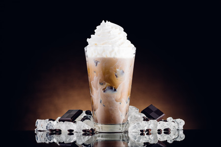 Iced coffee in glass and crushed ice on brown background