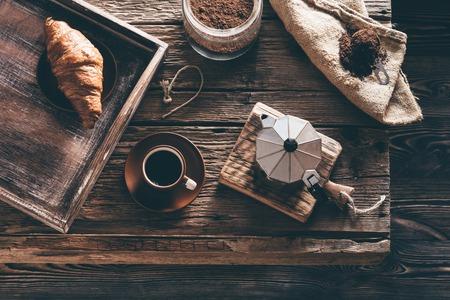 コーヒー カップや窓の光を夜に古い木製のテーブルに食材