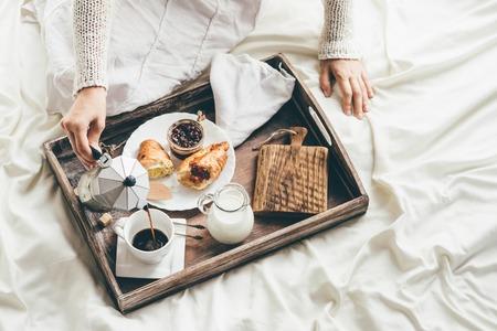 petit dejeuner: Femme ayant petit déjeuner au lit. La lumière de la fenêtre