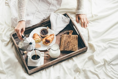 breakfast: Mujer que desayuna en la cama. Luz de la ventana