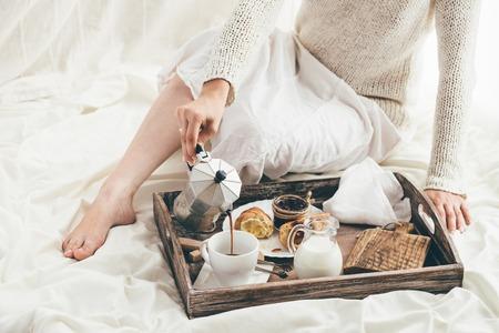 침대에서 아침 식사하는 여자. 창문