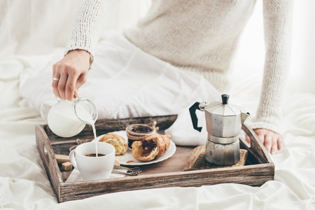 Vrouw met ontbijt op bed. Venster licht