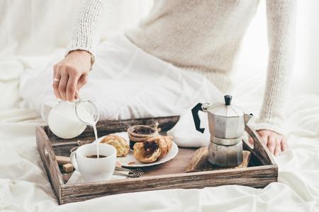 bed time: Woman having breakfast in bed. Window light