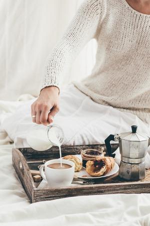 ベッドで朝食を持っている女性。窓の光