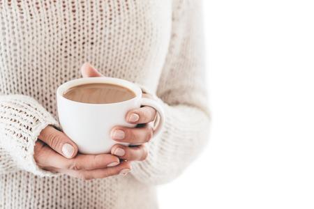Warming kopje koffie in de handen van vrouwen geïsoleerd Stockfoto